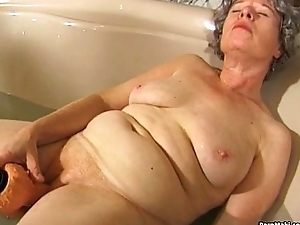 Granny masturbates with a fake penis in bathtub